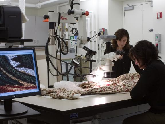 Conservators examining an Indian cotton dress