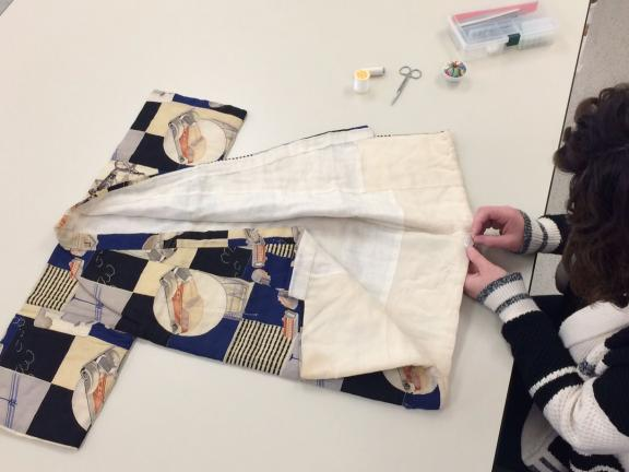 Sewing of the object label on a child's kimono