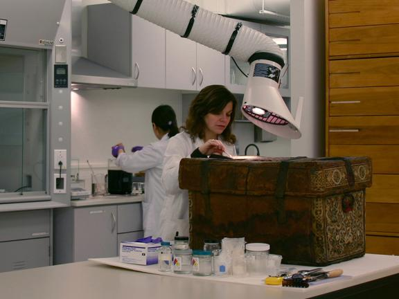 Conservator treating an embroidered trunk
