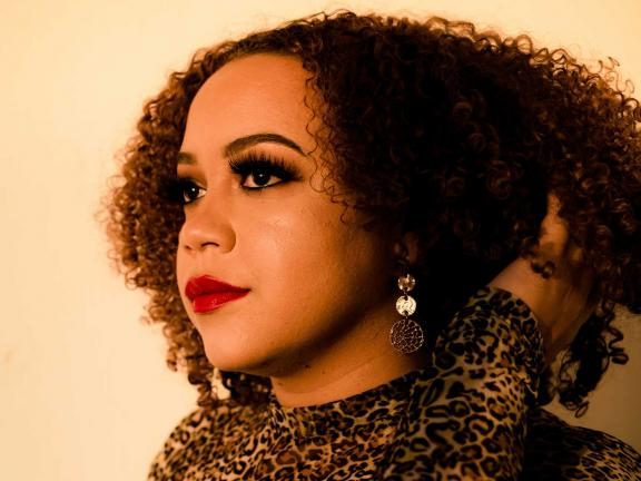 photo of DJ Slick Vick, girl with curly brown hair and red lipstick