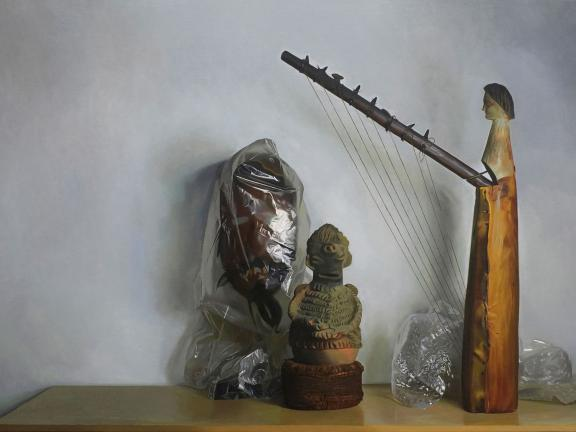 painting of stringed musical instrument on table next to small carved sculpture and mask wrapped in plastic