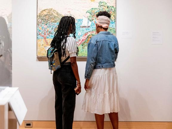 Two visitors looking at painting in an Art of the Americas gallery