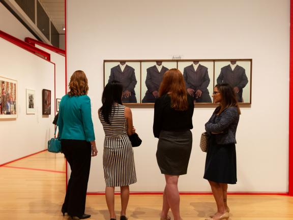 Four women looking at artwork
