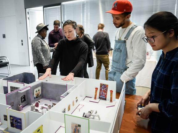 group of people looking at a miniature version of an exhibition