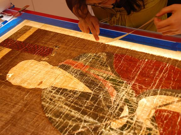 Conservator adding silk margins to reinforce the edges of a Korean painting, which is placed face down on a red lacquer light table