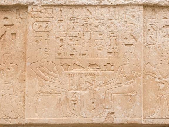 Egyptian door with etching of king and queen seated at a table