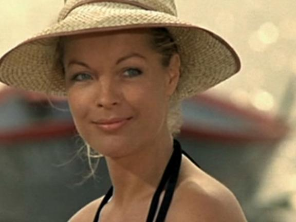 Still from César et Rosalie, depicting woman smiling, wearing a straw hat, at the beach