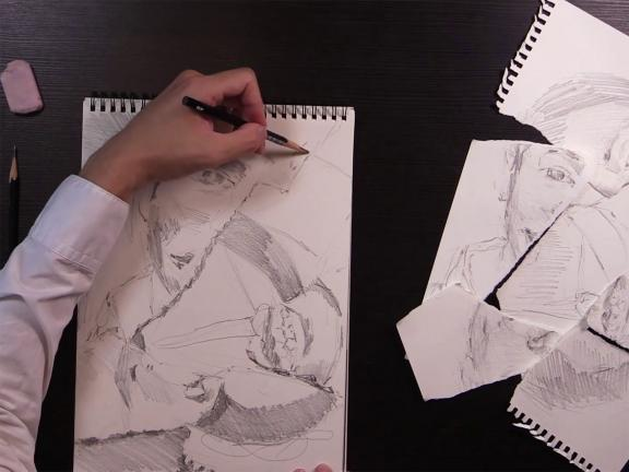 overhead view of table while artist sketches fragmented portrait on drawing pad