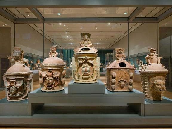 view of a gallery with six different urns on pedastals