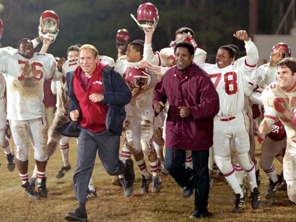 Film still from Remember the Titans of coaches running with football players
