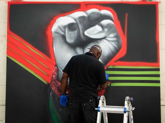 picture of a man spray painting a depiction of a fist on a wall