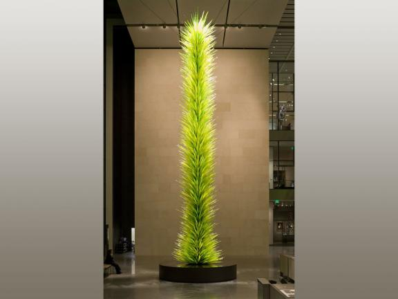 tall spikey green sculpture in the middle of a large room