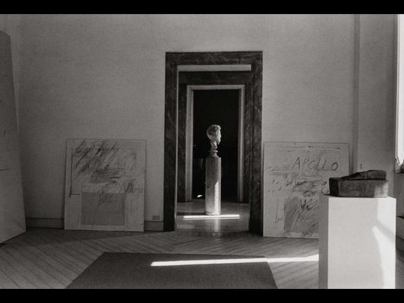 black and white photograph of a doorway with two abstract paintings and a Greek-style bust in the middle