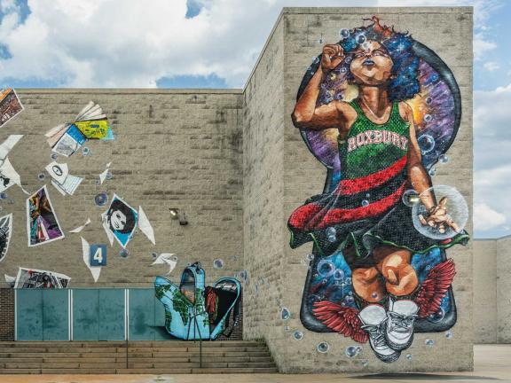 picture of a mural with little girl blowing bubbles surrounded by books