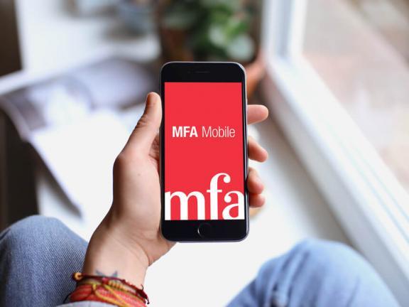Overhead view of held smartphone displaying MFA Mobile splash screen