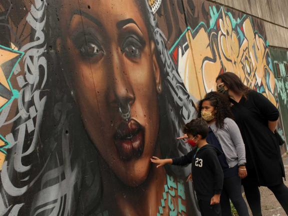 photo of a family standing in front of a large mural of a womans face with yellow graffiti-style writing
