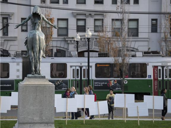 A sculpture of a Native American man on horseback stands on a pedestal in front of a passing MBTA Green Line trolley. Signs surround the sculpture with visitor thoughts on the work of art.
