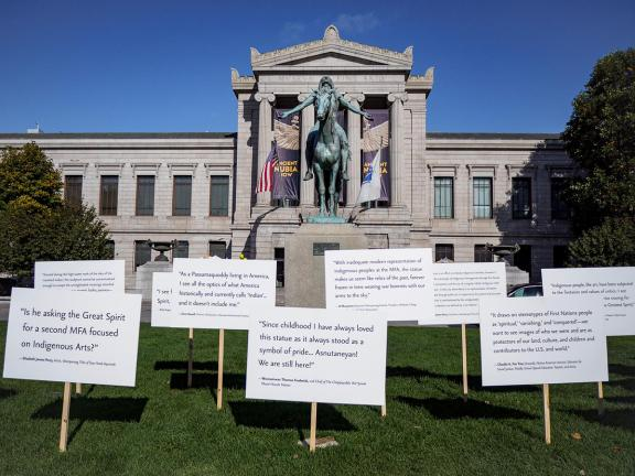 A sculpture of a Native American man on horseback stands on a pedestal in front of the MFA's Huntington Avenue Entrance. Signs surround the sculpture with visitor thoughts on the work of art.