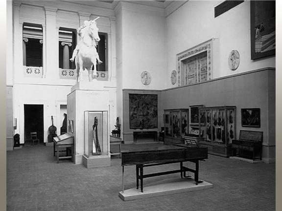 Black white photograph of museum gallery with musical instruments on display