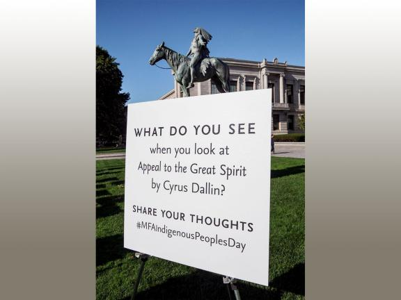 A sculpture of a Native American man on horseback stands on a pedestal. Signs surround the sculpture with visitor thoughts on the work of art.