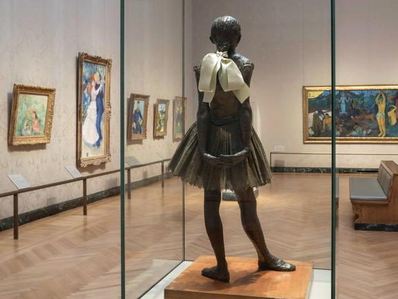 Degas sculpture of young dancer in foreground with impressionist paintings hanging on gallery walls in background