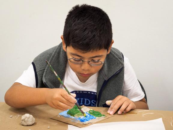Young boy adding painted details to a clay tile.