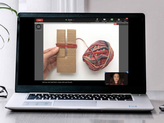 Laptop on table with yarn and cardboard for pompon making activity and MFA educator on screen.