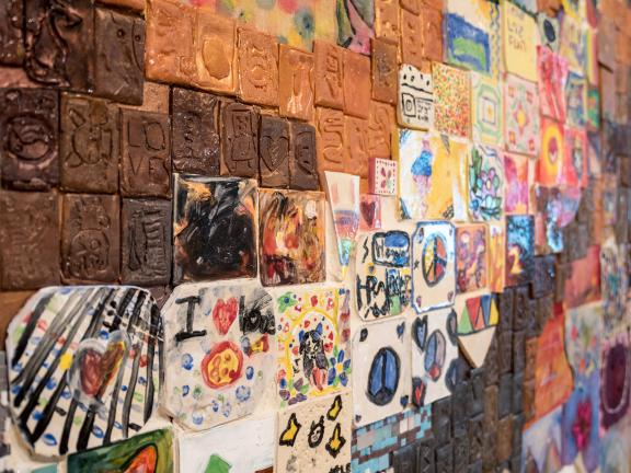 detail of multicolored relief sculpture made up of smaller works of art created by grade school students