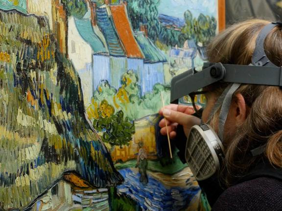 Conservator working on Van Gogh's House at Auvers painting using small brush