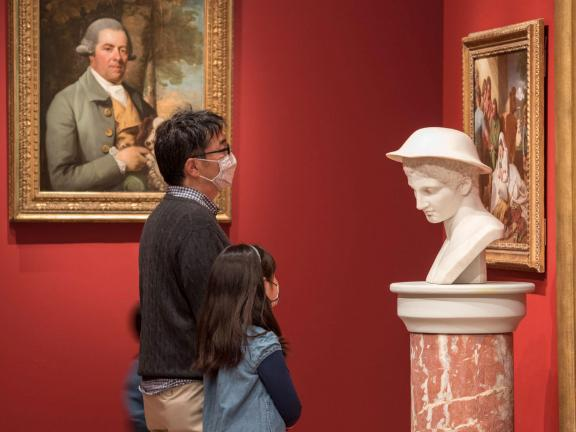 Parent and child looking at a bust on a pedestal in a gallery
