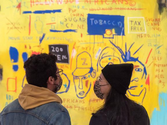 Couple wearing masks standing in front of Basquiat painting, Hollywood Africans