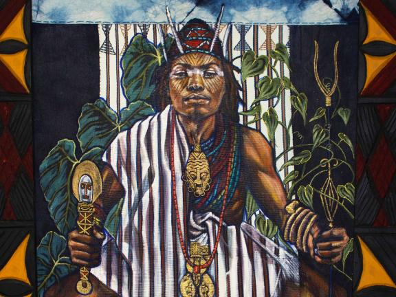 Portrait of a man with painted face in ceremonial costume holding scepters.