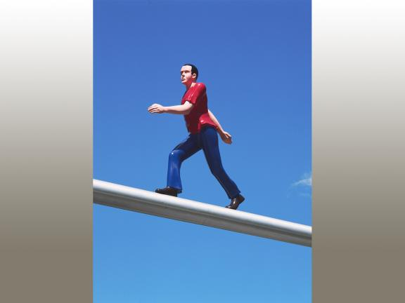 Photograph of sculpture of a man wearing a red teeshirt and blue pants walking on a pole.