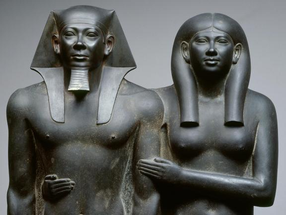 Dark grey statue of an Egyptian king and his wife with her arms wrapped around her husband.