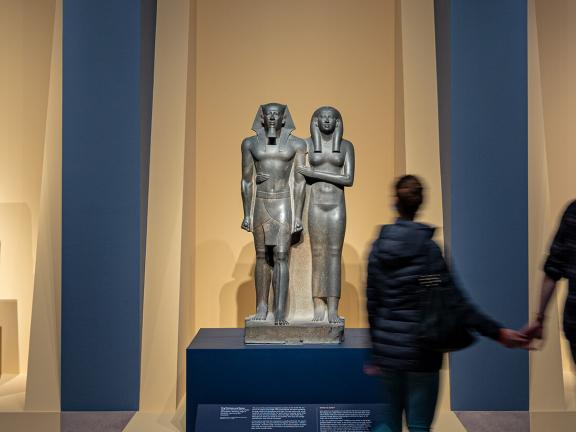 Two visitors holding hands looking at sculpture of Egyptian king and queen