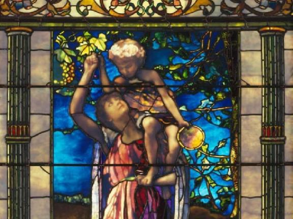 A stained glass window depicting a woman holding a young boy on her shoulder.