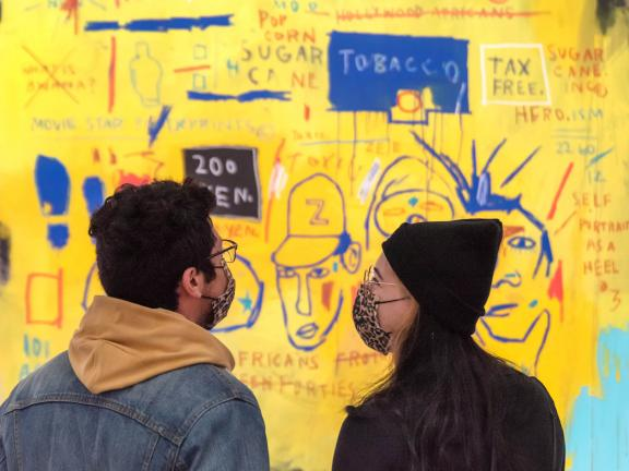 Two visitors wearing masks standing side-by-side and looking at the brightly colored Basquiat mural