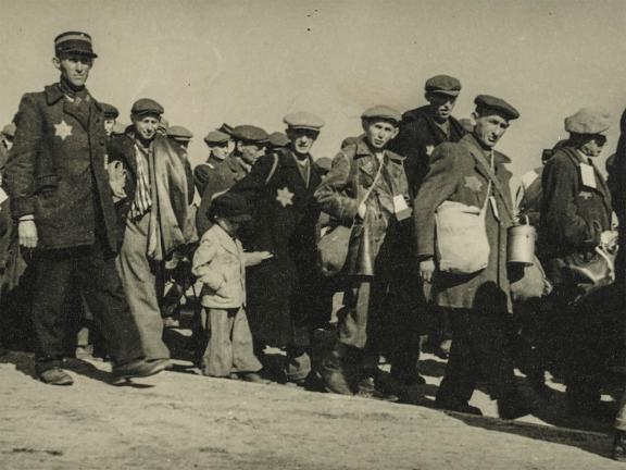 detail of historical black-and-white photograph depicting a column of Jewish men and children, some with visible Stars of David on coats
