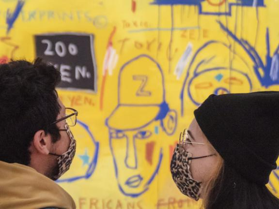 Two visitors wearing masks, looking at large Basquiat mural
