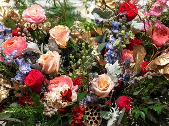An arrangement of flowers, featuring red, pink, and orange roses