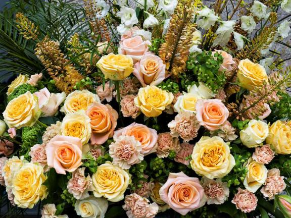 An arrangement of tightly bunched flowers, featuring pink and yellow roses
