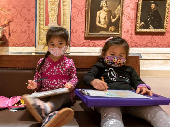 two young visitors in masks draw in the gallery