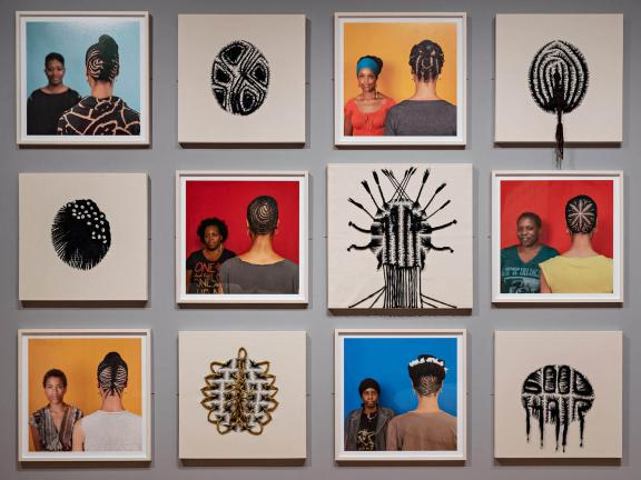 Grid of 12 framed artworks on gallery wall, alternating between photographs of hair stylists posing next to artist Sonya Clark, facing away so only her hair style is visible, and framed arrangements of hair weavings