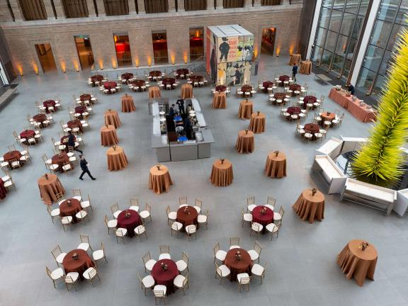 Photograph of large room filled with dining tables, chairs, and some waitstaff preparing for an event.
