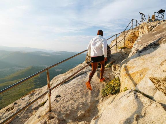Photograph of a man in running gear running up a steep rock with mountains in the distance