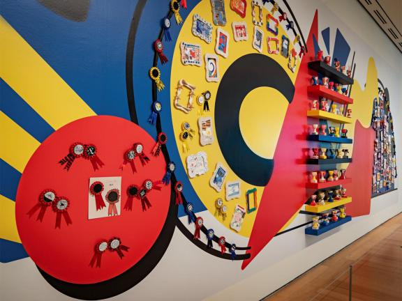 Red, yellow, and blue mural of various shapes with small sculptures and ribbons attached to the wall alongside it.