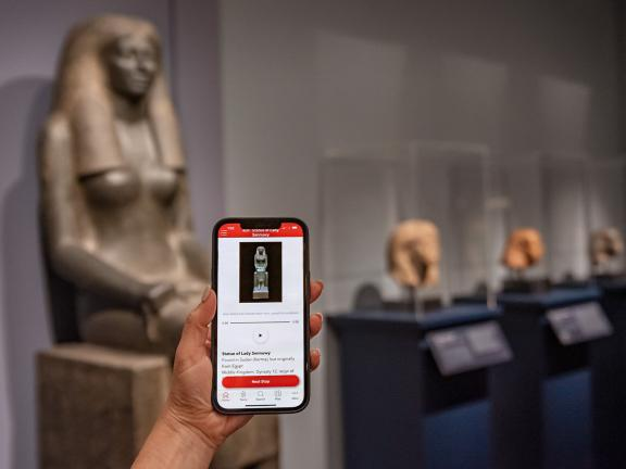 Smartphone with MFA Mobile app on screen, held up in front of Egyptian sculptures in background