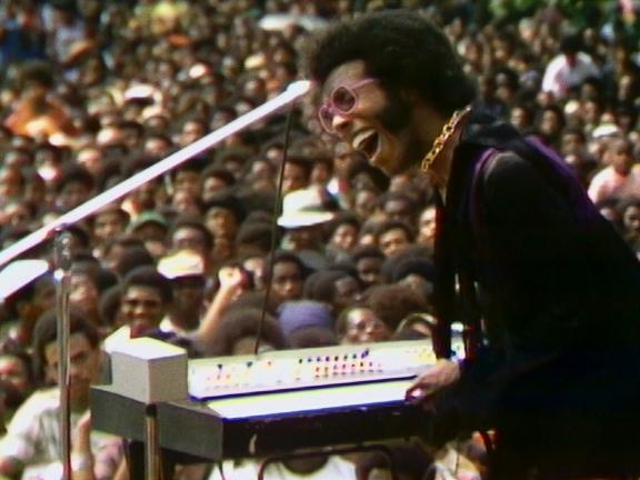Sly Stone playing a keyboard and singing at a very crowded concert
