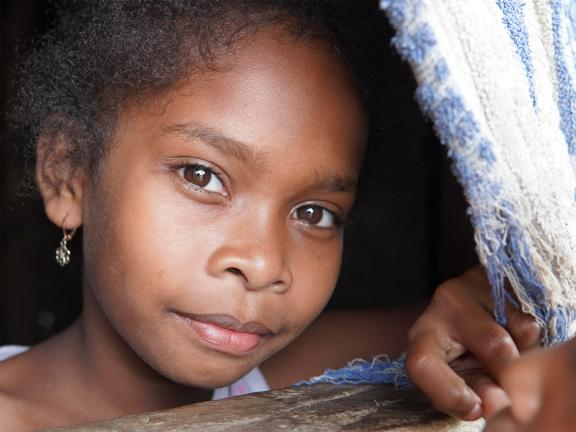 Close up photograph of a young girl looking out of a curtained window