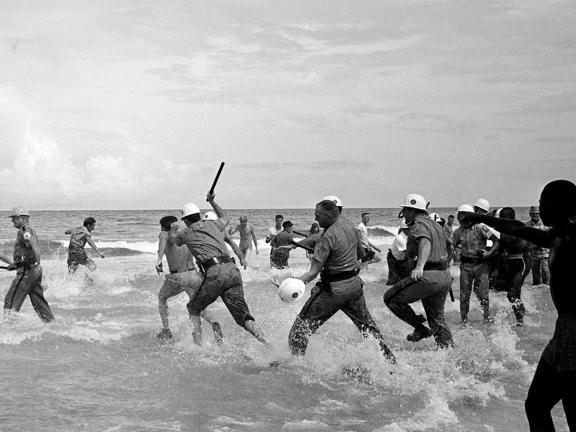 Black and white photograph of a group of men being chased into the water by officers beating them with batons
